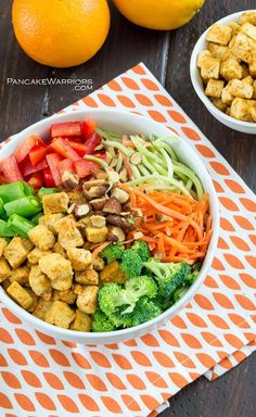 Crispy crunchy orange tofu in an Asian inspired Buddah bowl.This mountain of fresh veggies will fill you up without weighing you down. The orange tofu is seriously addicting and will soon be your new favorite dish! Vegan, gluten free and easy to make! | www.pancakewarriors.com