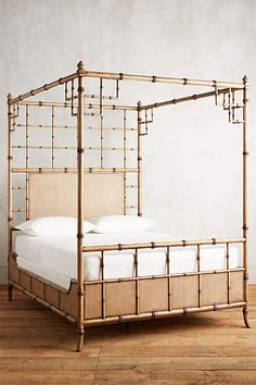 rattan cane frame four-poster bed. OMGGGG. anthro.