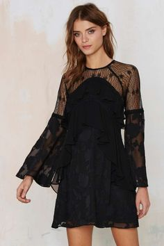 The Shoshanna Dress is black and features a sheer lace top with crew neck, asymmetric ruffles at front, chiffon floral burnout and amazing bell sleeves.