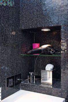 """Une niche munie d'un spot et d'une tablette en verre a été créée pour les accessoires courants. Le mitigeur """"Hansa Canyon XS"""" (Hansa) installé latéralement fait gagner de la place. Interrupteurs et prise """"Axolute Nighter"""" (Bticino) noirs lumineux, coordonnés avec la mosaïque."""