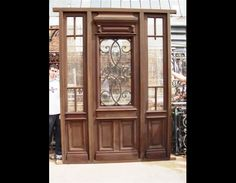 Antique Single Entrance door with wrougth iron insert and sideligths. It comes with beveled glasses installed.
