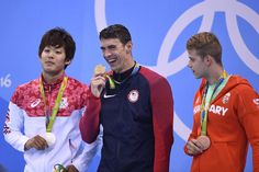 USA's Michael Phelps (C) poses on the podium with silver medallist Japan's Masato Sakai (L) and bronze medallist Hungary's Tamas Kenderesi after he won the Men's 200m Butterfly Final during the swimming event at the Rio 2016 Olympic Games at the Olympic Aquatics Stadium in Rio de Janeiro on August 9, 2016.   / AFP / GABRIEL BOUYS
