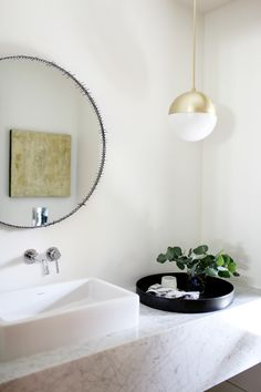 Marble and brass powder room in a remodeled Ralph Anderson 1966 home in Bellevue, Washington, by interior designer Lisa Staton and builders Lochwood-Lozier, photo by Belathée | Remodelista