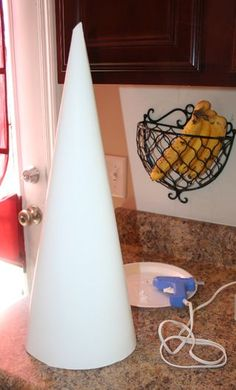 Here's a great crafting tips:  If you are making something that requires a cone, make your own out of poster board.  I only suggest this when you're using the cone as a base to glue something on to and not stick things in to (styrofoam cones can get expensive, especially the large ones).  Poster board is sold at the dollar store.  Cut a square, roll up and glue together. Then cut around the bottom to create an even stable cone.