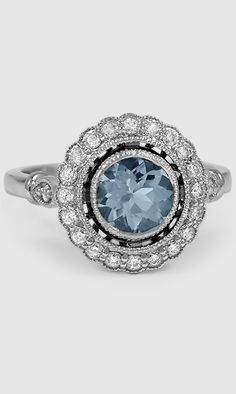 This stunning ring features a unique aquamarine surrounded by a halo of diamonds.