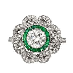 Art Deco diamond and emerald dress ring, centering on a circular-cut diamond weighing approximately 1.00 total carats with a calibre-cut emerald surround to a delicately pierced, interlaced diamond-set 'ribbon' frame, with partway diamond-set band, mounted in platinum. Via 1stdibs.