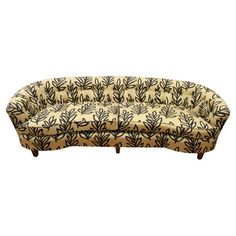 Mid-century arched sofa with tufted upholstery in a leaf motif.    Product: Sofa  Construction Material: Wood and...