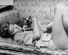 Alfred Eisenstaedt - Aspiring ballerina Edwina Seaver relaxing on sofa at home with pet Siamese cat Ting Ling - 1940