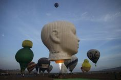 Hot air balloons are prepared for a flight as others take off during an international hot air balloon festival at Maayan Harod National park in northern Israel September 30, 2015. REUTERS/Baz Ratner