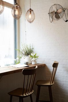 A vintage fan and mixers turned pendant lights help set the mood in New York's chicest cafe, Maman. | Lonny.com
