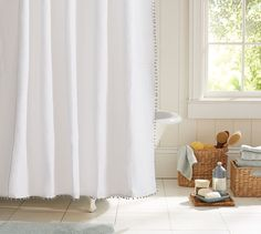 Pom Pom trim on shower curtain. Could do this for plain window panels as well. Cute for a girl's room.
