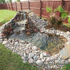 Backyard pond framed by rocks #pondplanet #ponds...