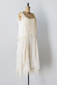 1920s ivory silk lace chiffon flapper dress. This beautiful feather light formal dress features hankie hemline, draping on hips that meets at the back with a lovely little bow, and stunning cream colored lace work that decorates the front and back of this dress. The inner dress is crafed of luxurious crepe feel silk and hooks and snaps to close. Sideway