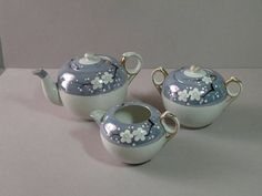 This vintage Japanese lusterware tea set features a matching teapot, sugar dish, & creamer. The pattern features blue luster with black tree branches budding to white flowers with green centers. The bottom of the set is white & has gold trim. The teapot measures 4.5 inches tall x 7.5