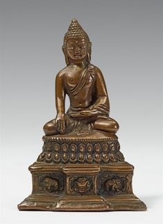 A Kashmiri bronze figure of Buddha Shakyamuni. 16th/17th century  A Kashmiri bronze figure of Buddha Shakyamuni, seated with his hands in bhumisparsa mudra on a lotus base on a stepped elephant and dragon throne, wearing a sanghati, the face with silver-inlaid eyes and urna, the bronze with a smooth deep brown patina. Base plate probably later. 16th/17th century.  Height 11.2 cm