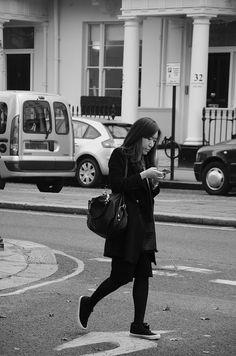 Women checking mobile phone, Victoria, London SW1, 19th Nov 2014