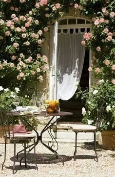 Door into courtyard, framed with pink climbing roses , an drape/curtain inside and garden table and chairs.