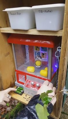 Carnival games meet geocaching! Control the crane to pick up a capsule and drop it down the chute. Does it have the log sheet? Pop it back through the hole in the front glass when you're done. Go to the linked Twitter post to watch the geocache in action!  #IBGCp