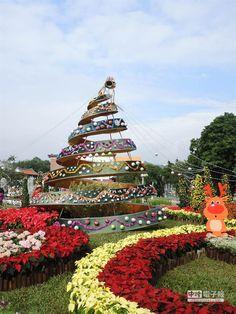 公園處園藝管理所設計的「歡滾吧!彩虹耶誕」展區,將聖誕樹打造成旋轉造型,掛上許多裝飾小物之餘,周圍也種滿各式聖誕紅和草花。(張潼攝)
