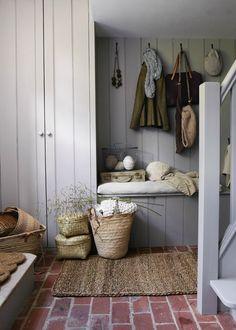 Une entrée dans une maison de famille avec un banc et des paniers de rangement