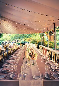 Soft pink linens and pink roses, candles and the tent is strung with lights to create a romantic mood