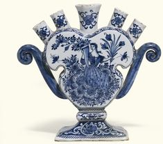A Dutch Delft blue and white tulip vase, early 18th century of spade form with scroll handles surmounted by five nozzles, painted on one side with Flora holding a cornucopia of flowers, the reverse painted with bird amongst lush foliage, painted mark CLV and numerals 10 and 18,