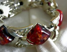 Stunning Coro bracelet with red confetti stones in a bright silver tone setting. Signed CORO. Measures 7 1/4 inches long. Heavy and well made, it