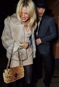 Sienna Miller wearing a cream outfit with vintage fur jacket and animal printed bag