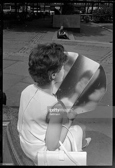 New York, NY- Rhoda Schneider, of Forest Hills, Queens, NY, uses a reflecting face tanner to triple the effect of the already bright- and hot -New York sun in Bryant Park here, June 21st. The first day of summer brought sweltering 90-degree temperatures to the humid city. BPA2#4856