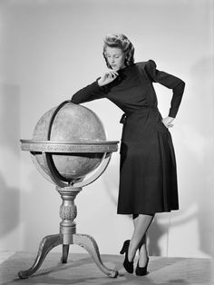 A model wearing a black woollen Utility Atrima dress in 1943. A model leans on a large globe as she shows off her black woollen Utility Atrima dress, costing 11 coupons. 1940s Fashion Women, Vintage Fashion, 1940's Fashion, Classic Fashion, Timeless Fashion, Fashion Clothes, Retro Fashion, Fashion Trends, Hardy Amies