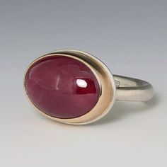 A sterling silver and 14K yellow gold Jamie Joseph ring set with a smooth oval indian ruby on an egyptian band Stone measures 13.5mm x 16.9mm.