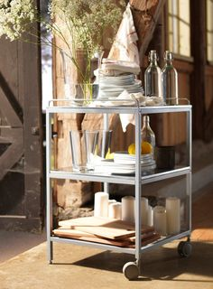 An IKEA cart can be filled with all your party table decoration essentials such as extra flowers, bottles of water, extra lemons, candles, glasses, plates and chopping boards.