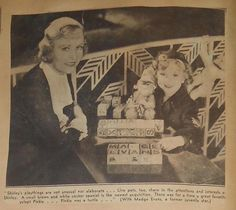 1934 Shirley Temple has some sort of elf-like doll in this clipping with Madge Evans, her Stand Up & Cheer co-star.