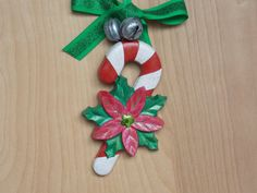 """OOAK Wood Wall Art by Lend Me Your Eyes Art Studio: This hand painted candy cane, Xmas decoration is a great mesh of traditional Xmas beauty with a new """"kitschy,"""" twist. The mixed media artistic flare with bells and ribbons makes this Christmas Wall Ornament a MUST have! The colors are bright and the poinsettia is stunning with the various colors giving this piece that """"BLING"""" factor."""