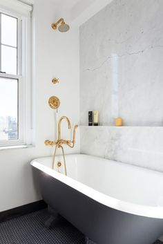 Bathroom with marble walls, brass accents, and a clawfoot tub
