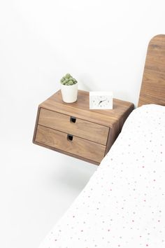"""Sleek and contemporary solid wood hand crafted bedside table / nightstand floating drawer The nightstand is designed to float on the wall, attached to the wall , its a moderately easy install for someone with basic tools (drill, and a screwdriver) A matte acrylic varnish is applied to the wood, leaving the pore open and applying natural wood oil to protect. MATERIALS American oak American black walnut White lacquered american oak MEASUREMENTS 1 Drawer Wide 18.3"""" / 46.5 cm De..."""