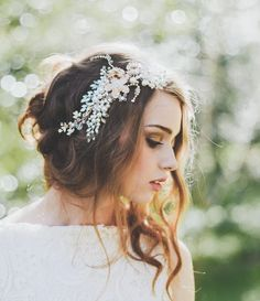 Low bun of wavy hair at the back, tucked up under embellished hairpiece with front pulled out and draped