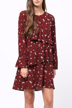 0d600ebf15f5 Classic floral printed burgundy shift dress tiered with ruffles and  features a crew neckline and long. Shoptiques