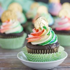 Pot of Gold Cupcakes. Dark Chocolate Cupcakes with the Rainbow Striped Frosting, and a Gold Coin on top!