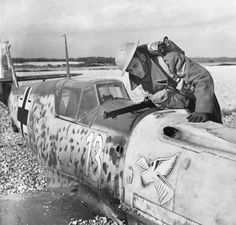 This Messerschmitt Bf 109E-1 piloted by Unteroffizier Arno Zimmermann was downed after a Brirish Hurricane fired a machine gun burst through the engine. The pilot headed back to the French coast, but the engine faltered badly, the cockpit filled with smoke, and he was obliged to make a forced landing on the beach gravel near the water tower at Lydd, Kent (October 27, 1940). It is seen being inspected by a Home Guard sentry. Zimmerman remained a POW for the duration of the war.