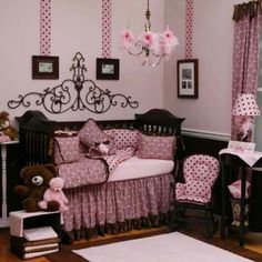 nursery ideas - love the black and pink color scheme and the polka dots and the beautiful swirly rod iron decor above crib and the ribbon strips hanging from ceiling down to pictures.