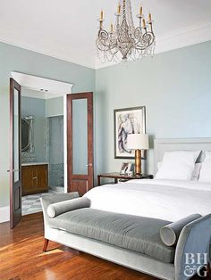 New furnishings bring an elegant, modern twist to this bedroom. A chandelier adds drama, and the casual bed prevents the traditional elements from making the room too stuffy. Pale gray-blue walls are a soothing touch.