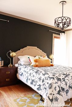 Tips for creating an eclectic chic space with bold prints and bright colors.  This room features a stunning black accent wall, gray trim and beautiful accessories from HomeGoods.