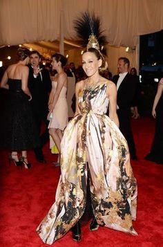 Sarah Jessica Parker exagerou na combinação do vestido estampado Giles Deacon combinado com botas Christian Louboutin e um mega adereço na cabeça, com plumas e brilhos, assinado por Phillip Treacy.