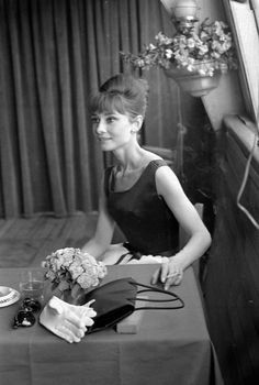 """The actress Audrey Hepburn photographed by Roger Viollet inside the boat """"Bateau Mouche"""", on theSeine, after a press conference for the publicity of her new movie """"Paris - When It Sizzles"""" in Paris (France), on July 16, 1962. Audrey was wearing: Dress:Givenchy(sleeveless, body of black satin and skirt of white silk, of his haute couture collection for the Spring/Summer of 1962). On the table: Sunglasses:Oliver Goldsmith(created especially for her in 1956. The same ..."""