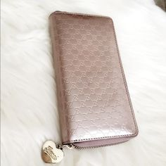 100% Authentic Gucci Pink Wallet Cute Light Pink Gucci Wallet up for sale. This zip around wallet has pretty gold Gucci hearts Charm attached. The light pink leather interior consists of twelve card sections, and  a zip compartments for coins . In Very Excellent condition. Comes with dust bag and Box! Gucci Bags Wallets
