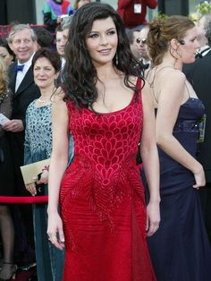 76th Academy Awards - 2004  The following year, Zeta-Jones's gown was a rich red, with a touch of plumage from Atelier Versace by Donatella Versace. The tank-style silk chiffon gown featured an ornate Swarovski crystal front.