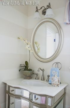 Half Bath Makeover on a tiny budget at www.viewalongtheway.com  She got the mirror and vanity at Homegoods.  She painted the wall and then painted stripes in a Valspar pearlescent glaze.  Found the faucet for $40 online.