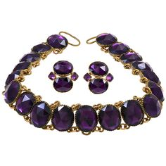 "Antique ""Queen Anne"" Suite of Necklace and Earrings. ""Queen Anne"" amethyst paste necklace and earrings set in gilt metal. This style of jewelry was misnamed for Queen Anne, who reigned from 1695 to 1714, as it was made in the mid 18th century. The vivid purple paste stones used are faceted as rose cuts. The earrings have back to front fittings and fit close to the earlobe. The necklace is fastened with a ribbon. circa 1750."