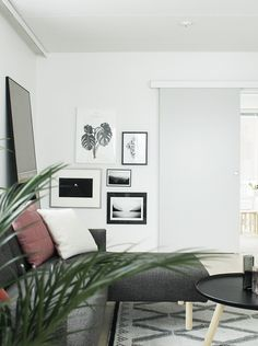 Crisp and white living room with dark sofa and tall leaning mirror